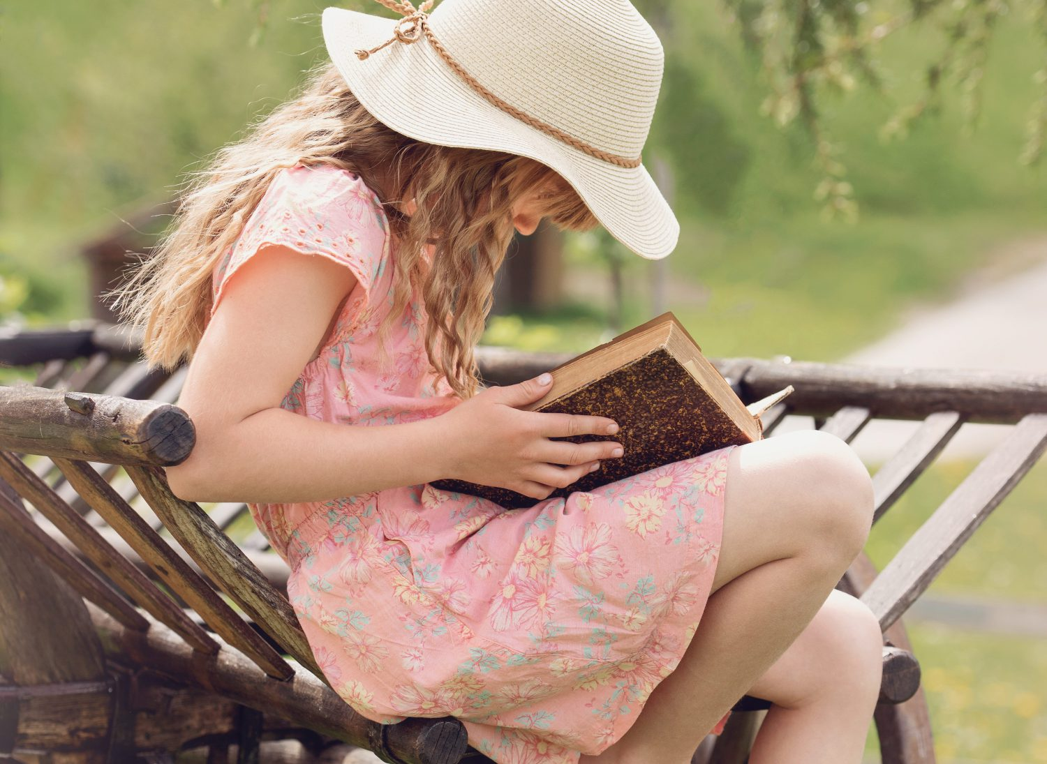 Child reading a book in garden